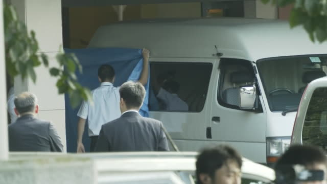 Aerial shot of a white van type vehicle / The vehicle going inside the crematory facility Japan's Justice Ministry is preparing to hand over the...