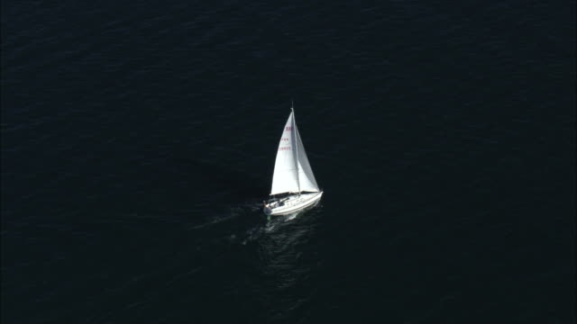 Aerial shot of a yacht sailing across the water.