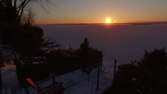 4K aerial shot of a young girl photographing a frozen Lake Champlain in Vermont in the winter