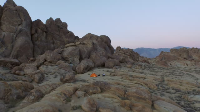 Aerial shot of a young man backpacker camping with his dog in a mountainous desert.