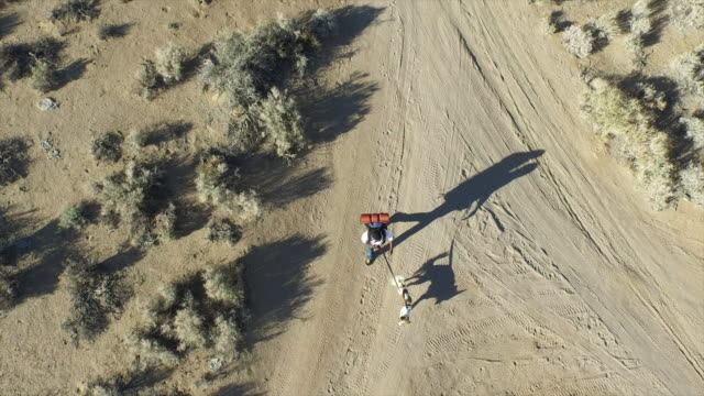Aerial shot of a young man backpacking with his dog on a dirt road in a mountainous desert.
