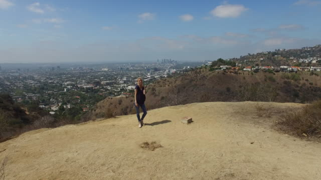 A 4K aerial shot of a young woman standing on a hill near Los Angeles, in 4K