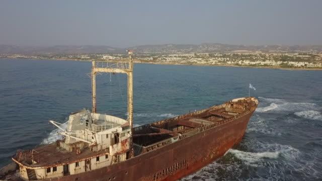 vídeos y material grabado en eventos de stock de aerial shot of abandoned cargo ship wreckage in sea near city, drone flying forward towards coastline against sky - paphos, cyprus - bandera griega
