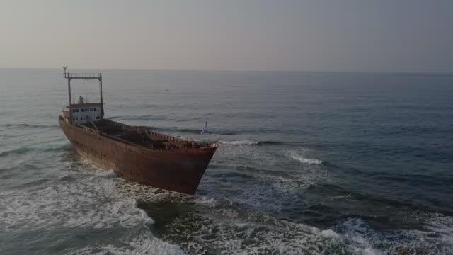 vídeos y material grabado en eventos de stock de aerial shot of abandoned shipwreck with greek flag in sea, drone flying backward from damaged ship against sky on sunny day - paphos, cyprus - bandera griega