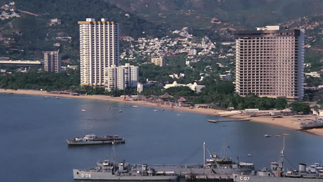 vídeos de stock e filmes b-roll de aerial shot of acapulco bay in 1979 - 1970 1979