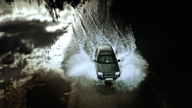Aerial shot of an off road vehicle driving on a flooded road.