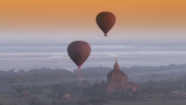 Aerial shot of ancient temple and hot air balloons