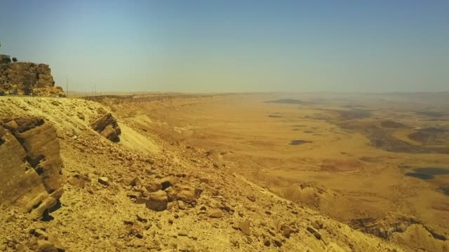 aerial shot of arid landscape in desert against sky on sunny day, drone flying forward over rocky mountain - mitzpe ramon, israel - dürre stock-videos und b-roll-filmmaterial