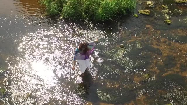 vídeos de stock, filmes e b-roll de aerial shot of asian woman paddling in shallow river - vadear