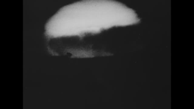 Aerial shot of atomic bomb explosion / shot on board ship of bright flash from explosion and men wearing protective goggles watching explosion /...