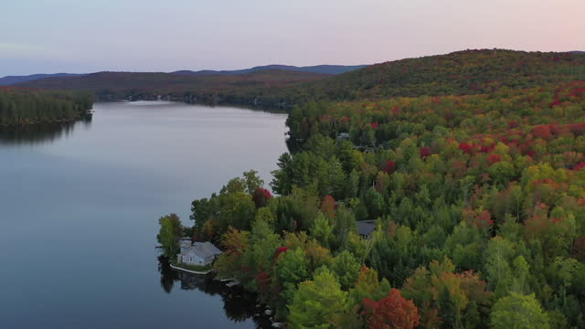 aerial shot of autumn trees by calm lake against sky during sunset, drone flying forward over water - lake groton, vermont - vermont stock videos & royalty-free footage