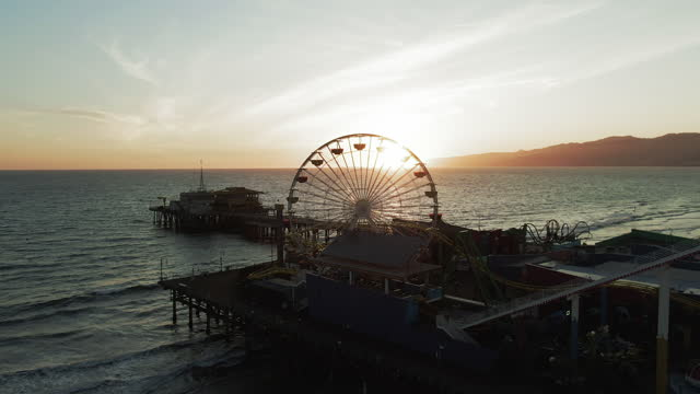 vídeos de stock e filmes b-roll de aerial shot of back lit ferris wheel at santa monica pier, drone flying backward from famous landmark over sea against sky at sunset - back lit