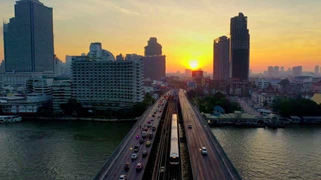 チャオプラヤー川、bts とバンコク市内の空中ショット スカイ鉄道とジャルンクルン通りにタークシン橋日の出 - クワッドコプター点の映像素材/bロール
