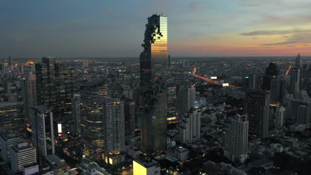 luftaufnahme von bangkok city, central business von drohne in der dämmerung erschossen - hochbahn passagierzug stock-videos und b-roll-filmmaterial