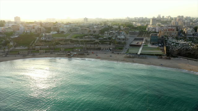 aerial shot of beach in city against sky during sunset, drone flying backward from cityscape - jaffa, israel - jaffa stock videos & royalty-free footage