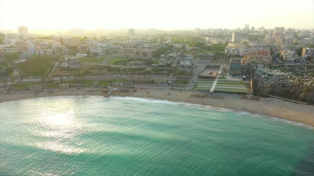 aerial shot of beach in city against sky during sunset, drone flying forward towards cityscape - jaffa, israel - jaffa stock videos & royalty-free footage
