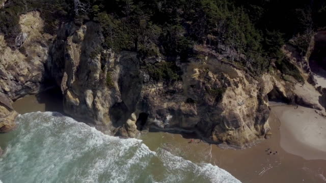 aerial shot of beach on oregon coast with cliffs and ocean waves - sunny video stock e b–roll