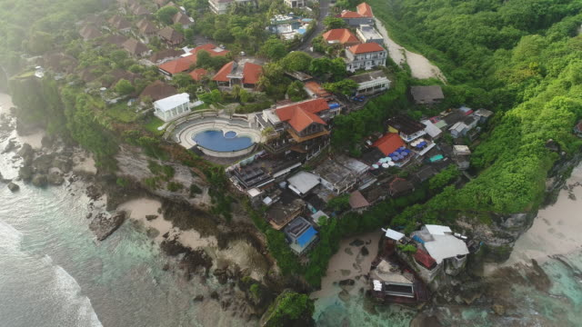 aerial shot of beach town in bali - felswand stock-videos und b-roll-filmmaterial