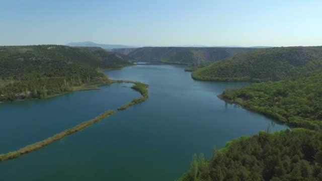 stockvideo's en b-roll-footage met aerial shot of beautiful river amidst green mountains against sky, drone is moving backwards - krka, croatia - achterstevoren