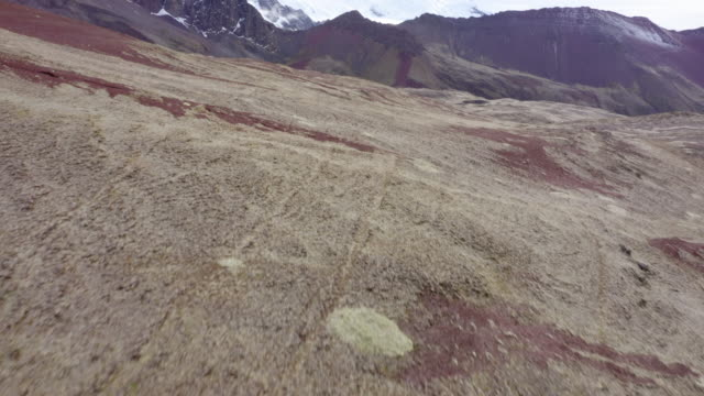 aerial shot of beautiful rocky mountains against sky, drone moving forward over barren landscape approaching pond - rainbow mountain, peru - snowcapped mountain点の映像素材/bロール