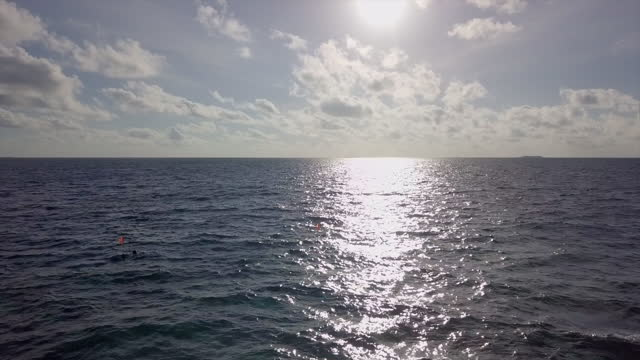 aerial shot of beautiful seascape against sky on sunny day, drone flying forward towards horizon - south male atoll, maldives - horizon over water stock-videos und b-roll-filmmaterial