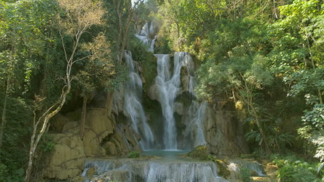 aerial shot of beautiful waterfall amidst green trees in forest, drone flying backward from cascade - luang prabang, laos - head back stock videos & royalty-free footage