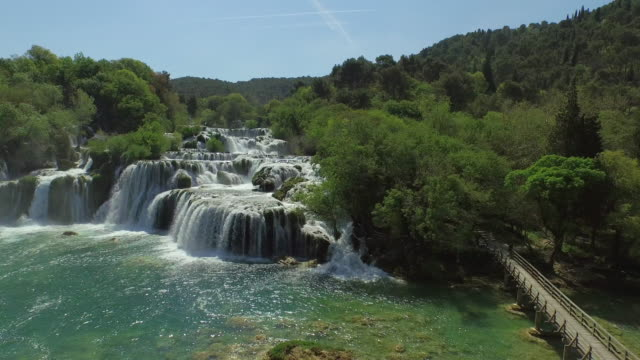 aerial shot of beautiful waterfall in forest, drone is descending over river - krka, croatia - waterfall stock videos & royalty-free footage