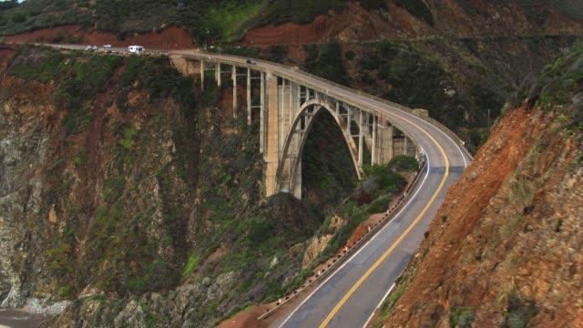 aerial shot of bixby creek bridge flying behind ridge - bixby creek bridge stock videos & royalty-free footage