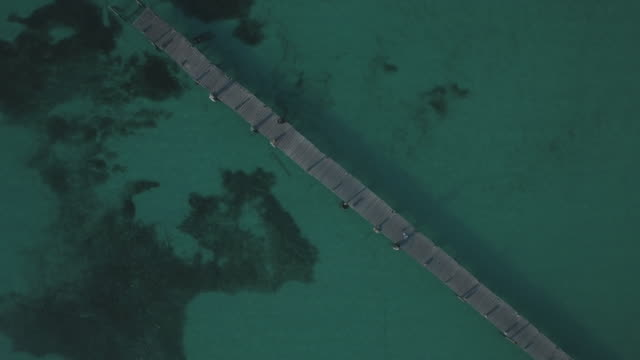 vídeos de stock e filmes b-roll de aerial shot of boardwalk in ocean - riviera maia