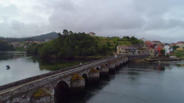 vídeos y material grabado en eventos de stock de aerial shot of boats anchored in the river ascending up and over a stone bridge in pontevedra, pontevedra, spain - piedra material de construcción