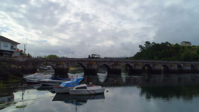 aerial shot of boats anchored in the river ascending up and over a stone bridge in pontevedra - anchored stock videos & royalty-free footage