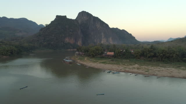 stockvideo's en b-roll-footage met aerial shot of boats moored at riverbank near village against sky, drone descending over mountains during sunset - mekong river, laos - vachtpatroon