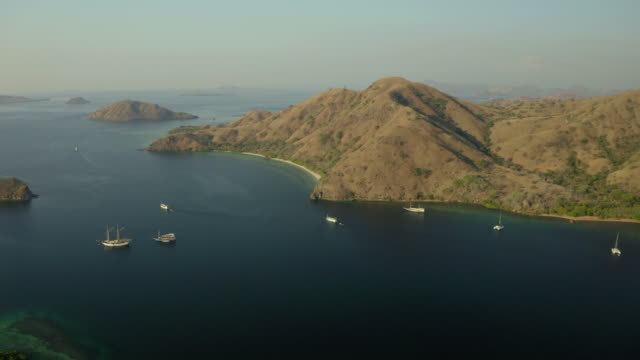 aerial shot of boats on sea near mountain range during sunny day, drone flying forward over nautical vessels against sky - komodo island, indonesia - komodo island stock videos & royalty-free footage