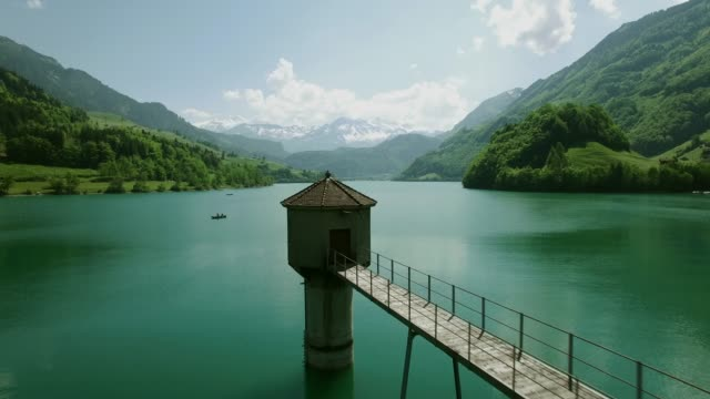 aerial shot of bridge over mountain lake with beautiful alps in the background - environment stock videos & royalty-free footage