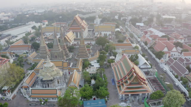 aerial shot of buddhist temple by street in city during sunset, drone flying backward from famous landmark - bangkok, thailand - bangkok video stock e b–roll
