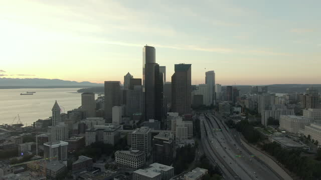aerial shot of buildings in downtown by dr jose p rizal bridge, drone flying backward over modern city by elliott bay against sky at sunset - seattle, washington - elliott bay stock videos & royalty-free footage