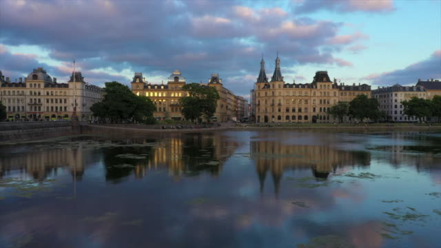 aerial shot of buildings reflection in lake against cloudy sky, drone ascending over water in city - copenhagen, denmark - denmark stock videos & royalty-free footage