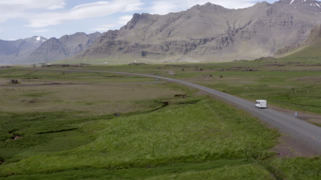 aerial shot of camper van moving on road amidst landscape, drone is flying forward over land - southwestern iceland, iceland - hay isolated stock videos & royalty-free footage