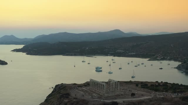 aerial shot of cape sounio in athens,athens, greece with the ancient temple of poseidon during the sunset at summer - temple building stock videos & royalty-free footage