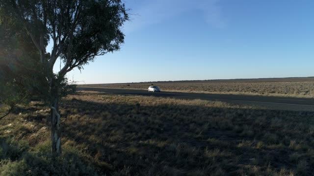Aerial shot of car driving on desert highway