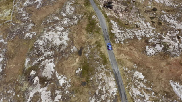 aerial shot of car on road amidst rocks, drone flying forward over vehicle - southwestern iceland, ireland - winter stock videos & royalty-free footage