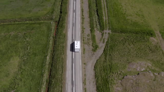 aerial shot of caravan moving on road amidst landscape, drone flying forwards over camper van amidst scenic land - southwestern iceland, iceland - road trip stock videos & royalty-free footage