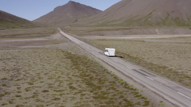 aerial shot of caravan moving on road towards mountains, drone flying forwards over vehicle amidst landscape - southwestern iceland, iceland - wohnmobil stock-videos und b-roll-filmmaterial