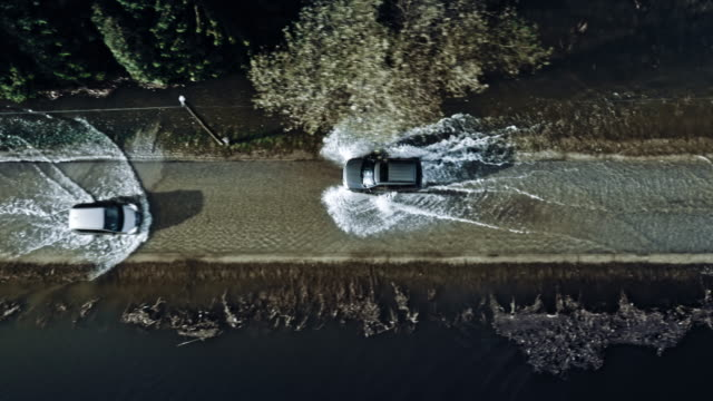 vídeos de stock, filmes e b-roll de aerial shot of cars driving on a flooded road - condições meteorológicas extremas
