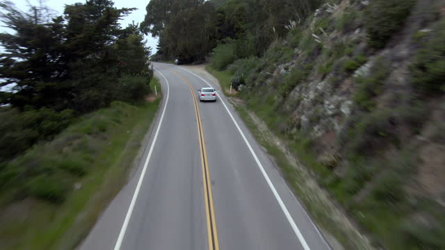 aerial shot of cars on winding mountain road amidst plants, drone flying forward over vehicles - big sur, california - winding road stock videos & royalty-free footage