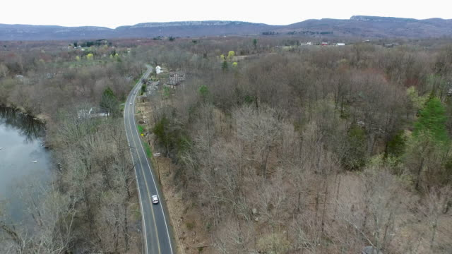 vídeos y material grabado en eventos de stock de aerial shot of cars winding along one lane road in upstate new york  - árbol latente