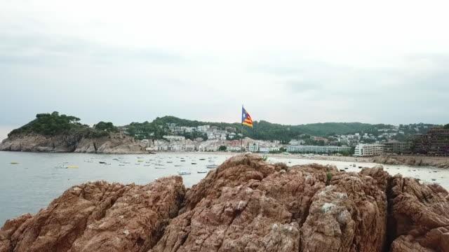 vidéos et rushes de aerial shot of catalan flag on rock formation by boats in sea, drone ascending over rocks by coastal city against sky - tossa de mar, spain - mar