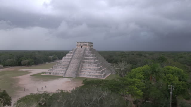 aerial shot of chichen itza amidst trees against cloudy sky, drone flying forward towards famous historic landmark - temple building stock videos & royalty-free footage