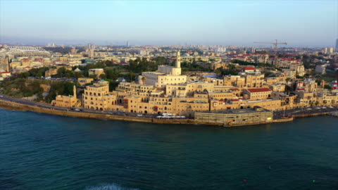 aerial shot of church in city by sea against sky during sunset, drone flying over water - jaffa, israel - ジャファ点の映像素材/bロール