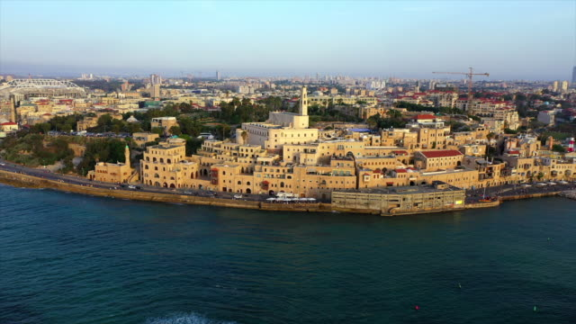 aerial shot of church in city by sea against sky during sunset, drone flying over water - jaffa, israel - jaffa stock videos & royalty-free footage